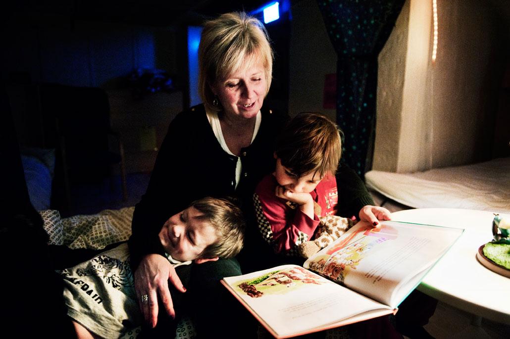 """""""Och snart satt de bakom kiosken och åt popcorn"""", läser nattisfröken Lena Löfqvist för Martin och León."""