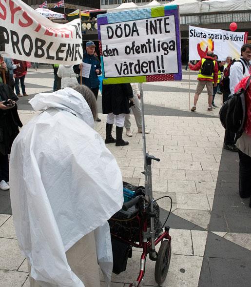 Döda inte den offentliga vården! En äldre kvinna hade fäst sitt plakat med det budskapet på sin rullator. Hon deltog när Kommunal i Stockholm manifesterade mot privatiseringar och nedskärningar i välfärden.