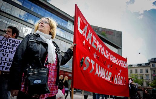 Elisabeth Ehn vid en av banderollerna på Sergels Torg. Anställda på Läkerols farbrik i Gävle, som ska flyttas till Slovakien, demonstrerade under torsdagen i Stockholm. Man marscherade från Sergels torg till Stureplan.