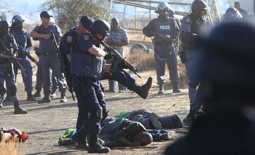 Polis omringar strejkande gruvarbetare efter att ha öppnat eld mot en folkmassa vid platinagruvan Lonmin nära Rustenburg i Sydafrika.