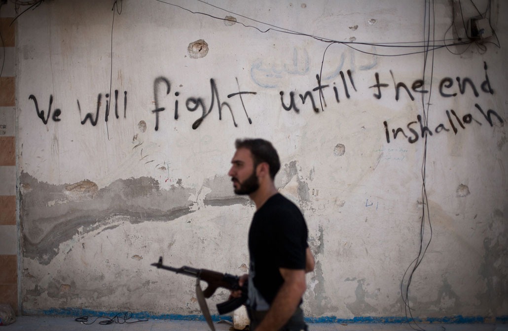 September 2012: En medlem i rebellgrupperna i FSA (Fria syriska armén) patrullerar i Aleppo, Syriens största stad med 3 miljoner invånare. Här pågår ett fullskaligt krig mellan FSA och regeringstrupperna, som vill återta kontrollen över staden. Det internationella samfundet är kluvet, och FN har hittills inte ingripit i konflikten.