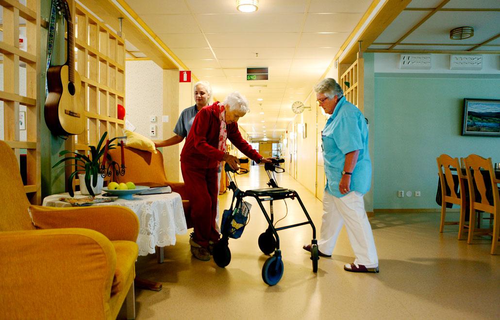 Det hårda golvet gav personalen ont i benen. Nu är det utbytt och besvären har minskat. Skyddsombudet Inger Arvidsson (till höger) och Linnéa Backlund hjälper Gunborg Nordin, 89 år.