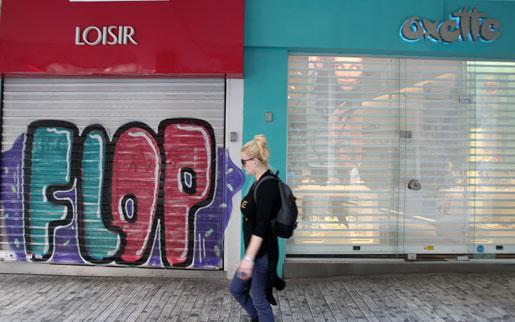 En fotgängare passerar en av alla stängda butiker i Athen på torsdagen.