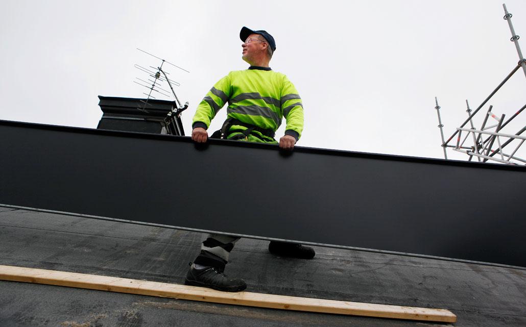 Vi behöver måttliga löneökningar och flexiblare anställningar för att klara oss genom lågkonjunkturen, skriver arbetsgivarna i plåtslageribranschen. Plåtslagare Bo Hallberg, som på bilden lägger nytt tak på ett hus i Hudiksvall, berättade i Arbetet i juni om sitt yrke.