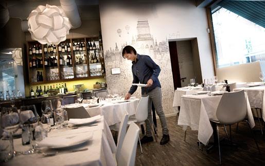 Servitör på restaurang Brazzerie Godot dukar bord.