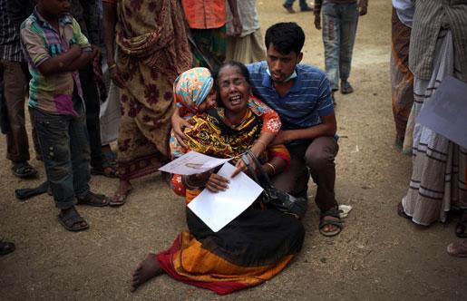 En sörjande kvinna i Dhaka tröstas efter att ha identifierat kroppen av dottern, som omkom när en niovåningsbyggnad rasade i slutet av april.