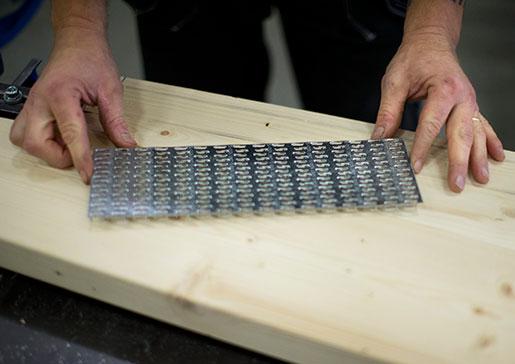 Plåt pressas in i träet för att takstolen ska kunna monteras ihop direkt på bygget. Foto: Björn Larsson Rosvall