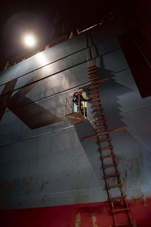 Ur en liten dörr på babords sida kliver lotsen Stefan Nilsson. Efter avslutat uppdrag med containerfartyget Edith-Maersk tar han sig – under gång – ner till lotsbåten via repstege.   Foto: Olof Ohlsson