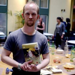 Johan Engman visar upp boken han medverkar i.