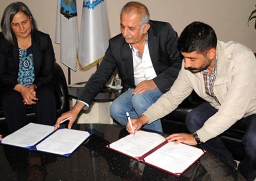 Borgmästaren Gultan Kisanak, Disks lokalordförande Serdar Ekingen och Kommunanställdas förbunds ordförande Salih Dogrul skriver under avtalet.