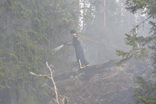 En brandman vid brandfronten vid Seglingsberg på onsdagen. När branden väl är släckt väntar eftersläckningsjobb i flera månader. Foto: Maja Suslin