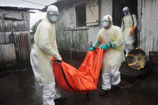 Sjukvårdspersonal i utkanten av Monrovia, Liberia tar hand om kroppen efter en kvinna som misstänks ha dött i ebola. Nu strejkar vårdpersonalen för att få en rimligare riskpremie för sitt arbete. Foto: Abbas Dulleh