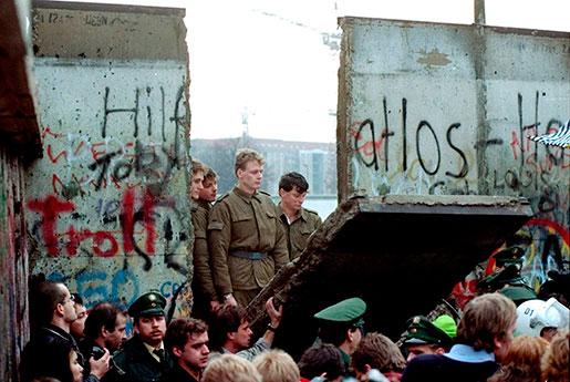 Östtyska gränsvakter ser på när muren rivs ner vid Brandenburger Tor. Fotot är taget den 11 november 1989. Foto: Lionel Cironneau
