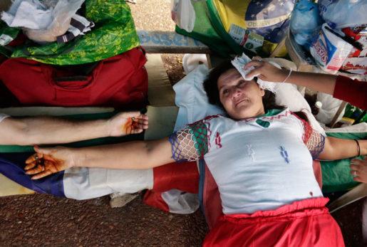 Rosa Caceres, 52, låter symboliskt korsfästa sig vid den brasilianska ambassaden i Asuncion, Paraguay. Foto: Jorge Saenz