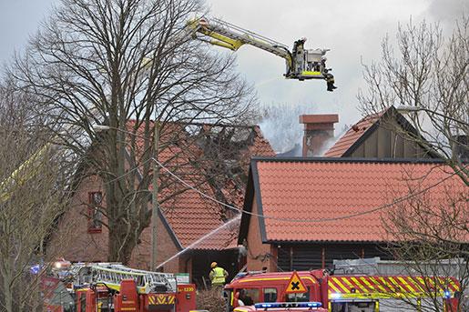 Brandmän bekämpar den kraftiga vindsbranden i Kvarnby folkhögskola på lördagen. Foto: Johan Nilsson