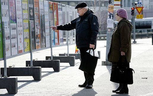 Finska väljare studerar valaffischerna i Helsingfors. Vilket parti kan lyfta ekonomin? är den stora frågan. Just nu verkar Centerpartiets stimulanspolitik få mest förtroende. Foto: Heikki Saukkomaa