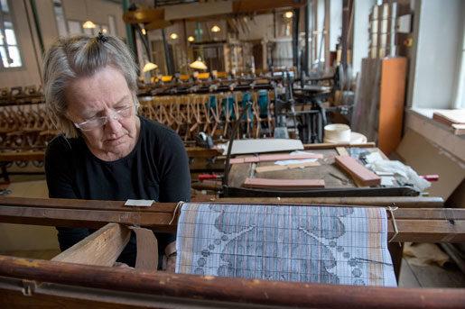 Eva Enbuske ser till att hålkortens mönster förs över till väven. 1,5 meter sidentyg om dagen kan hon producera.Foto: Maja Suslin