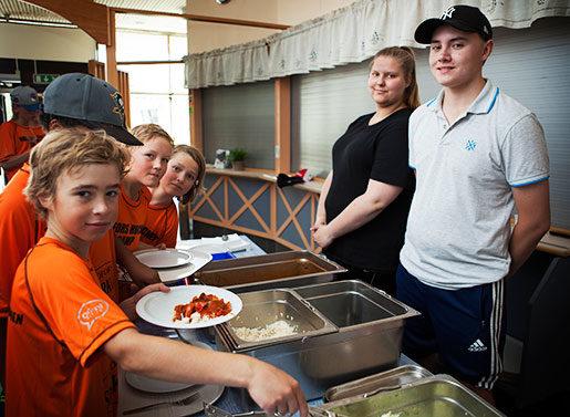 Hockeybarnen tar för sig av lunchen som serveras av Hanna Högnelid och Rasmus Bergqvist. Foto: Carl von Scheele