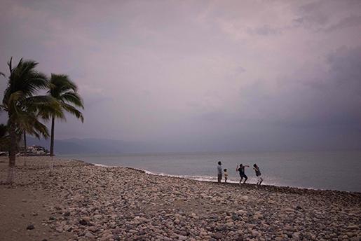 Turister slänger sten i havet i Puerto Vallarta i väntan på orkanen Patricias ankomst. Foto: AP / Cesar Rodriguez