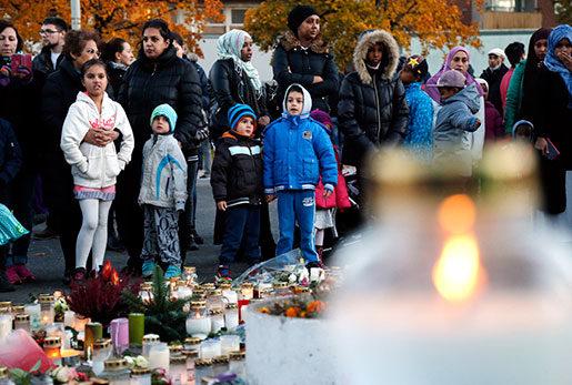 Ljus och blommor vid minnesplatsen utanför fritidsgården på skolan Kronan i Trollhättan. Två personer avled av sina skador när en knivman attackerade elever och personal på skolan i torsdags.