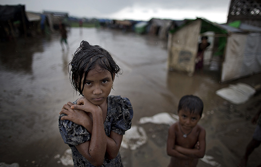 In this June 26, 2014 photo, a girl, self-identified as Rohingya, stands close to her family's tent house at Dar Paing camp for refugees, suburbs of Sittwe, Western Rakhine state,. Photo: AP /Gemunu Amarasinghe
