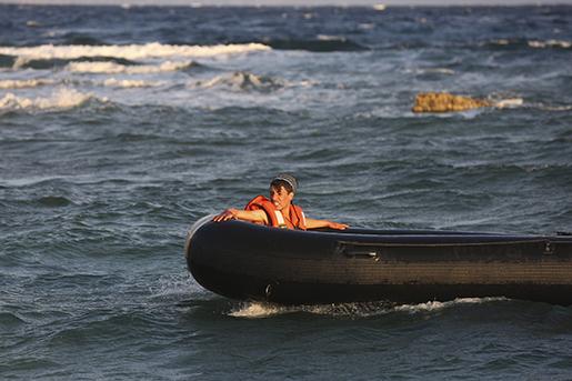 En flyktingbåt som just är på väg att lämna Turkiets kust (personen i båten har inget med texten att göra). Foto: AP Photo/Emre Tazegul
