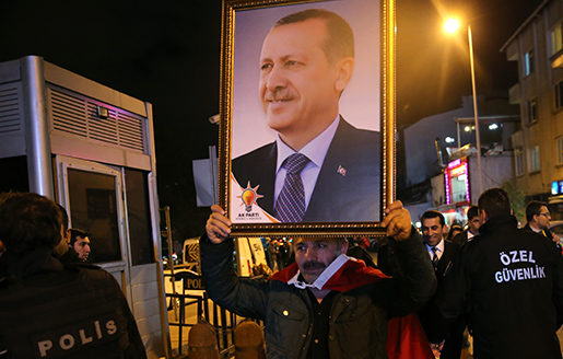 En AKP-sympatisör håller upp ett porträtt av president Erdogan. Foto: AP/Hussein Malla