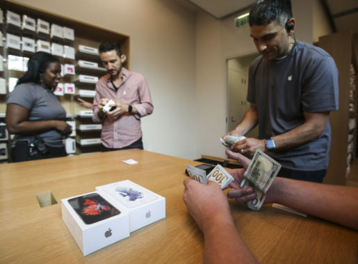 FILE - In this Sept. 25, 2015 file photo, a customer pays with cash for his Apple iPhone 6s and iPhone 6s Plus smartphones at the Apple store at The Grove in Los Angeles. Apple says it sold 13 million iPhone 6s and 6s Plus phones in the three days since its iPhone launch, topping last year's early sales mark. (AP Photo/Ringo H.W. Chiu, File)