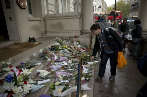 A man lays flowers for the victims of the deadly attacks in Paris, outside the French embassy in London, Saturday, Nov. 14, 2015. French President Francois Hollande said more than 120 people died Friday night in shootings at Paris cafes, suicide bombings near France's national stadium and a hostage-taking slaughter inside a concert hall. (AP Photo/Matt Dunham)