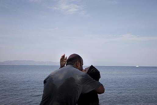 En man och kvinna kysser varandra efter att ha kommit fram med en gummibåt till den grekiska ön Lesbos. Foto: AP /Petros Giannakouris