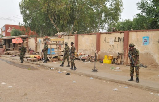 Soldiers stand guards at the scene of an explosion at a market in Kano, Nigeria. Wednesday Nov. 18, 2015. The suicide bomber exploded as truckers were tucking into dinner at the bustling marketplace where vendors urged them to buy sugar cane. At least 34 people were killed and another 80 wounded in Yola, a town packed with refugees from Nigeria's Islamic uprising, emergency officials said Wednesday. (AP Photo/Muhammed Giginyu)