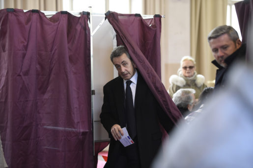"""Former French President and current French right-wing opposition """"Les Republicains"""" party leader Nicolas Sarkozy steps out of a polling booth before voting as part of the first round of the regional election at a polling station in Paris, France, Sunday, Dec. 6, 2015. French voters are casting ballots Sunday for regional leaders in an unusually tense security climate, expected to favor conservative and far right candidates and strike a new blow against the governing Socialists. (Eric Feferberg/Pool Photo via AP)"""