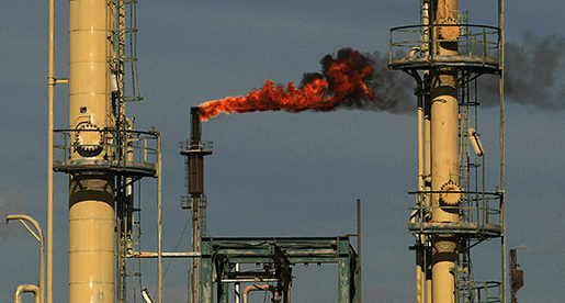 Fire shoots from a chimney at the Dura oil refinery outside Baghdad Saturday Feb. 22 2003. Iraq's oil reserves are the second largest in the world, after Saudi Arabia. (AP PHOTO/Jerome Delay)