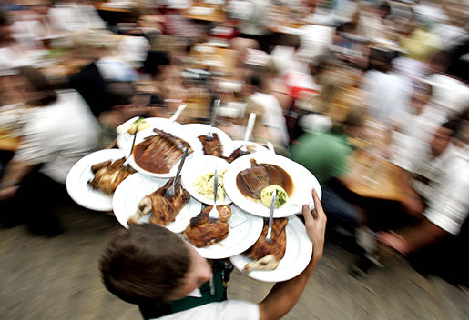 A waiter serves food during the last day of the 173rd Oktoberfest beer festival in Munich, southern Germany, on Tuesday, Oct. 3, 2006. (AP Photo/Christof Stache)