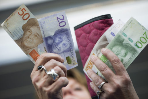 STOCKHOLM 201510 Kvinna med plÂnbok och de nya svenska sedlarna. Foto: Fredrik Sandberg / TT / Kod 10080