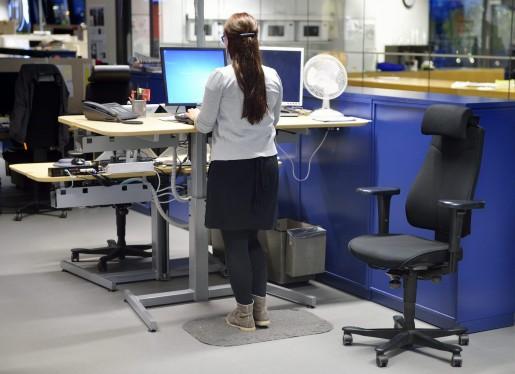 STOCKHOLM 20141017 En kvinna stÂr vid ett hˆj- och s‰nkbart skrivbord och jobbar Foto: Henrik Montgomery / TT / kod: 10060