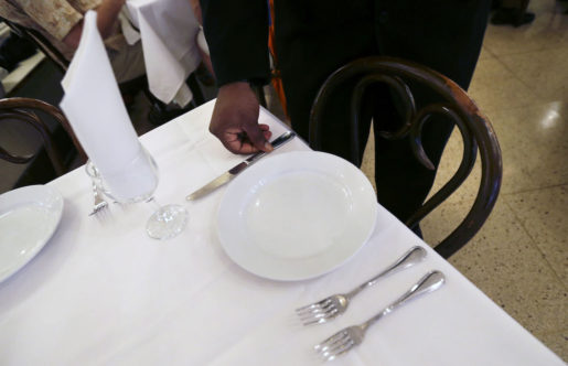 Waiter Geoffrey Parms sets a table at Antoine's Restaurant in New Orleans, Friday, Sept. 11, 2015. The restaurant last year reached its pre-Katrina sales of about $10 million. Next week it will hold a series of events to celebrate its 175th anniversary. The highlights include a visiting chef from Delmonicoís in New York who will team up with Antoineís Chef Mike Regua to offer special menus, a block party with a brass band and a Prohibition-themed gala. (AP Photo/Gerald Herbert)