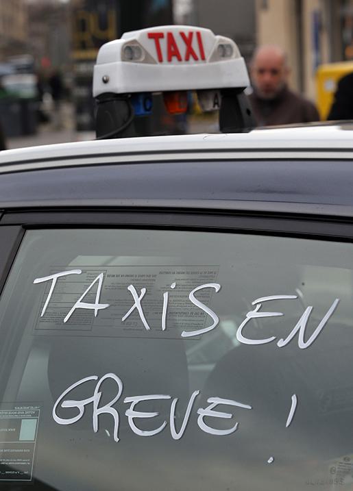 Taxibilar i strejk! står det på en taxi i huvudstaden Paris på tisdagen. Foto: AP Photo/Christophe Ena
