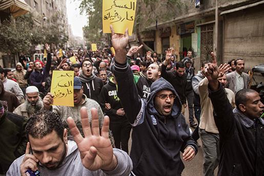 """Anhängare till Egyptens avsatte president Mohamed Morsi demonstrerar i Kairo på måndagen. På en av lapparna står det """"Militärregimen är en skam och ett förräderi"""". Foto: AP Photo/Belal Darder"""