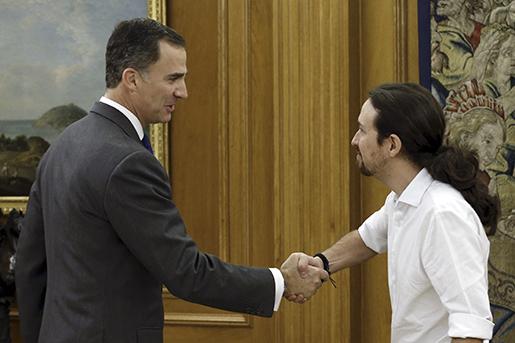 Spaniens kung Felipe VI, till vänster, skakar hand med Podemos ledare Pablo Iglesias. Foto: Angel Diaz, Pool Photo via AP