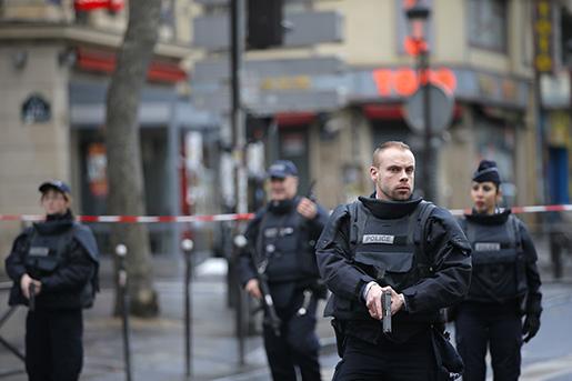 Polis med dragna vapen vid polisstationen i norra Paris. Foto: AP Photo/Christophe Ena