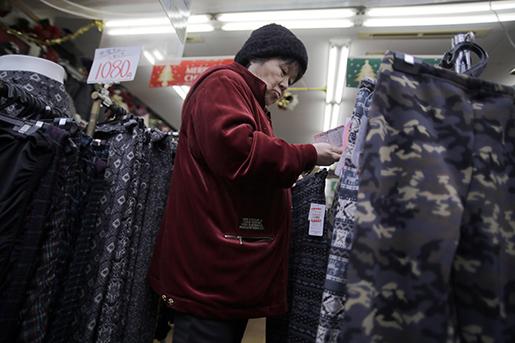En kvinna tittar på kläder i en butik i Tokyo, Japan. Regeringen manar företagen att höja lönerna, så att fler kan shoppa. Foto: AP Photo/Eugene Hoshiko