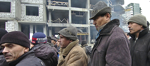 Construction migrant workers stand next to an unfinished building they worked on during a strike in the Ural Mountains city of Yekaterinburg, about 1500 kilometers (900 miles) east of Moscow, on Wednesday, Dec. 3, 2008. More than 100 migrant workers started a strike last week demanding pay for three months of work. Russia is grappling with its worst financial crisis in a decade, and companies across a range of sectors have announced a slew of job cuts as they hunker down to conserve cash. (AP Photo/Alexei Vladykin)