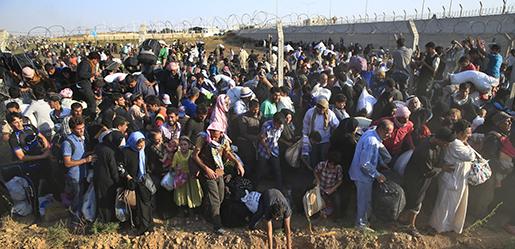 Juni 2015: Syriska flyktingar river ner stängslet till Turkiet och korsar gränsen. Flyktingar kommer att fortsätta vara i fokus, globalt såväl som i EU.Foto: Lefteris Pitarakis/TT