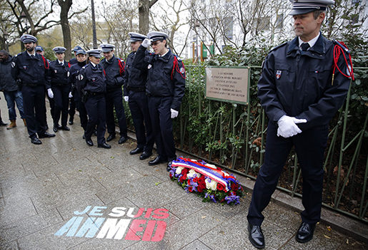 """Policemen stand next to spray painted on the sidewalk reading: """"Je suis Ahmed,"""" or """"I am Ahmed,"""" in the red, white and blue of the French flag near a plaque commemorating late police officer Ahmed Merabet in Paris, Tuesday Jan. 5, 2016. Hollande is honoring 17 victims killed in Islamic extremist attacks on satirical newspaper Charlie Hebdo, a kosher market and police a year ago this week, unveiling plaques around Paris marking violence that ushered in a tumultuous year. Police officer Merabet was killed as he tried to chase down the fleeing gunmen. (AP Photo/Christophe Ena)"""