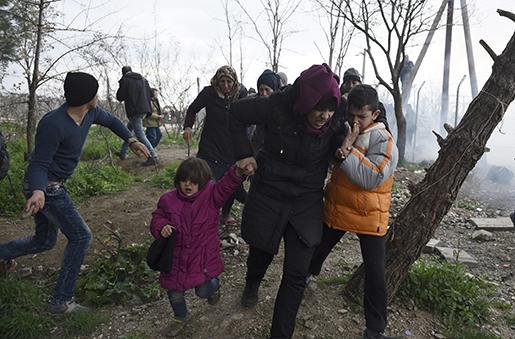 En kvinna flyr med sina barn, sedan makedonsk polis avfyrat tårgas över gränsen vid Idomeni. Minst 6 500 migranter väntar på att passera. Foto: AP Photo/Giannis Papanikos