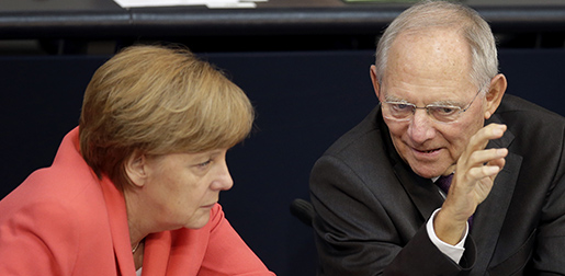 German Chancellor Angela Merkel, left, and German Finance Minister Wolfgang Schaeuble, right, talk during a meeting of the German federal parliament, Bundestag, in Berlin, Germany, Friday, July 17, 2015. Merkel urged German lawmakers Friday to vote in favor of a third bailout package for Greece, arguing that the cash-strapped country faces chaos without a deal. (AP Photo/Michael Sohn)