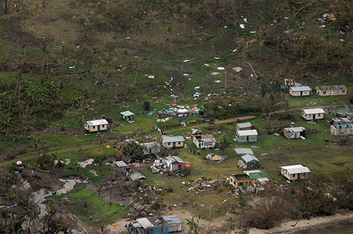 In this Sunday, Feb. 21, 2016 aerial photo supplied by the New Zealand Defense Force, debris is scattered around damaged buildings at Nakama settlement in Fiji, after Cyclone Winston tore through the island nation. Fijians were finally able to venture outside Monday after authorities lifted a curfew but much of the country remained without electricity in the wake of a ferocious cyclone that left at least six people dead and destroyed hundreds of homes. (New Zealand Defense Force via AP) EDITORIAL USE ONLY