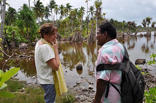 Miljö- och biståndsminister Isabella Lövin och Ngualuenga, borgmästare på Abaing, visar hur saltvattnet tränger in på land och dödar kokospalmer och viktiga grödor. Foto: Regeringen / TT