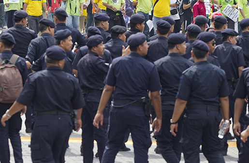 Police move to try and stop a group of protesters as they march through the central business district in Kuala Lumpur, Malaysia, Saturday, April 28, 2012. Thousands of people gathered near Kuala Lumpur's Independence Square to seek sweeping changes in polling regulations to curb fears of fraud in elections that many speculate will be held in June. (AP Photo/Mark Baker)